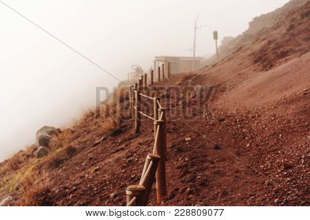 People Climb The Mountain On A Trail In The Fog