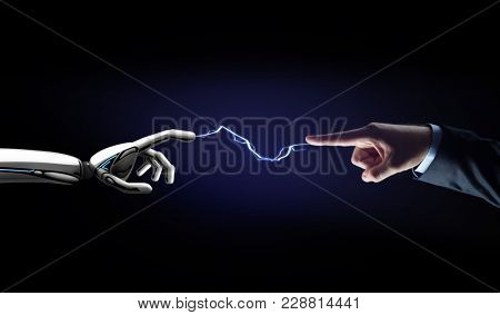 business, future technology and artificial intelligence concept - robot and human hand connected by lightning over black background