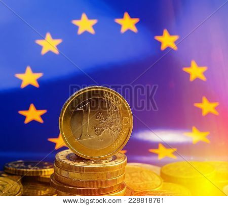 Pile Of Coins One Euro Against The Background Of The Flag Of The European Union. Business Metaphor.