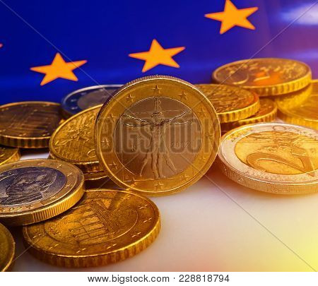 Coins Of Euro And Euro Cents Against The Background Of The Flag Of The European Union. Business Meta
