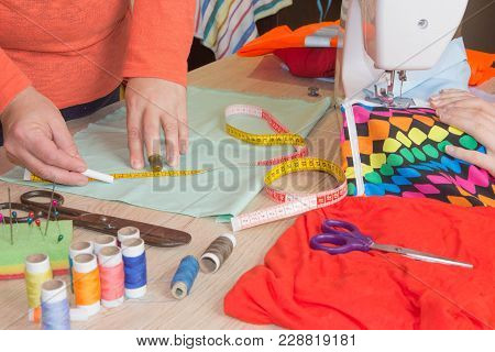 Woman's Hands Drawing A Pattern On Material At Her Workplace In A Tailor Shop. Clothes Designer At W