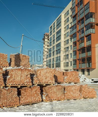 Piles Of Bricks Lying On The Ground Next To A Newly Built Dwelling House