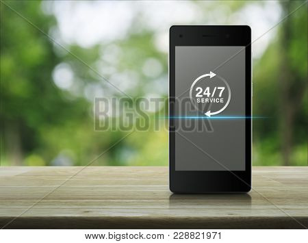 24 Hours Service Icon On Modern Smart Phone Screen On Wooden Table Over Blur Green Tree In Park, Ful