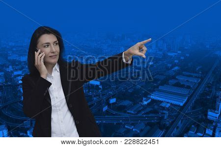 Caucasian Business Woman Talking On Her Cell Phone And Pointing Or Touching Touchscreen Over Modern
