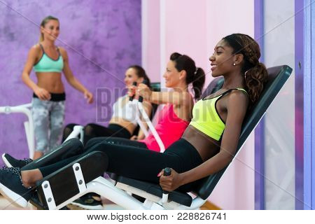 Happy young woman with a healthy lifestyle  doing exercise for toned legs while attending group workout class at a modern fitness centre for women