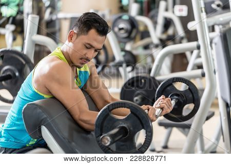 Young handsome man exercising bicep curls with the E-Z barbell while sitting down at preacher curl bench during upper-body workout routine