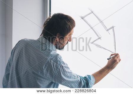 Businessman Drawing Arrow Pointing Down, Conceptual Symbol For Profit Loss And Failure In Business E