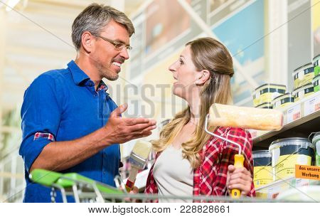 Home improver couple, woman and man, buying paint and painter tools for do-it-yourself project in hardware store
