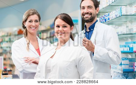 Team of apothecaries in pharmacy standing in front of shelf with prescription drugs