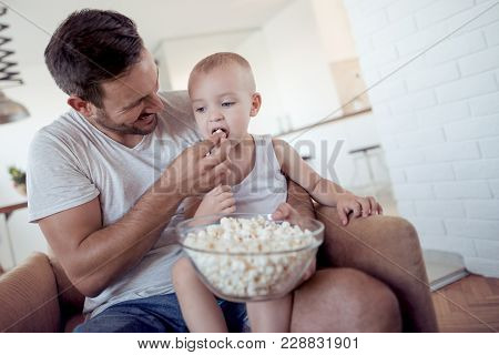 Happy Father And Little Son With Popcorn At Home