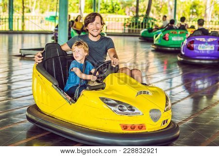 Father And Son Having A Ride In The Bumper Car At The Amusement Park.