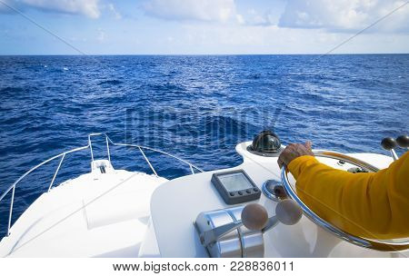 Hand Of Captain On Steering Wheel Of Motor Boat In The Blue Ocean Due The Fishery Day