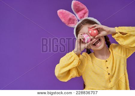 Cute little child wearing bunny ears on Easter day. Girl with painted eggs on bright purple background. Violet and yellow colors.