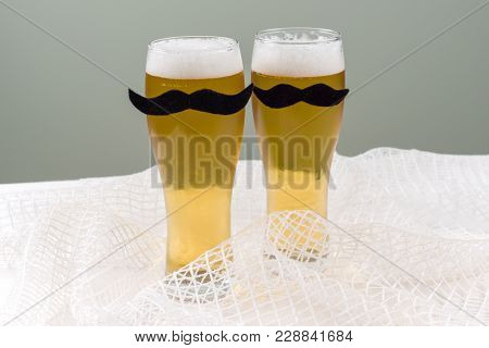 Two Glasses With Beer And A Symbolic Mustache. Background - Olive Wall, White Mesh Texture.