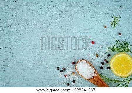 Coarse Sea Salt, Peppercorns, Lemon, Dill Over Blue Background