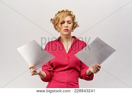 A Young Blonde Girl With A Lost View Looks At The Documents Spreading Her Hands In Front Of Her In C