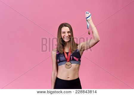 Successful Beautiful Girl Athlete On Isolated Background Shows Victory, Success, Medals. Attractive