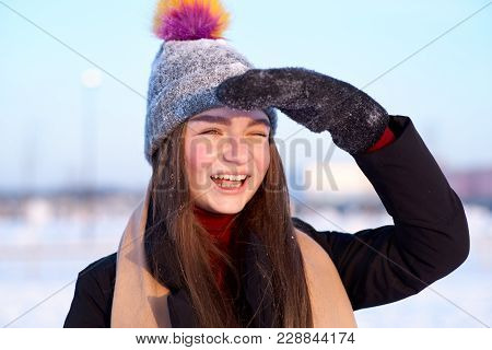 A Young Cheerful Girl In A Winter Hat And Mittens With A Joyful Playful Expression Closes Her Eyes F