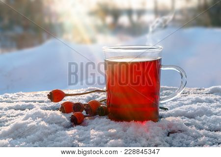 Hot Red Tea From Hibiscus And Rose Hip Fruits Outdoors In The Snow With Sunbeams, Healthy Warming Dr