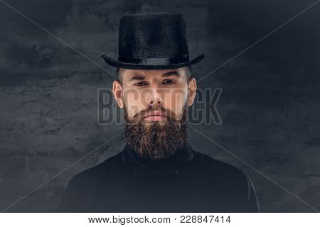 Portrait Of Bearded Hipster Male Dressed In A Black Shirt And A Cylinder Hat.