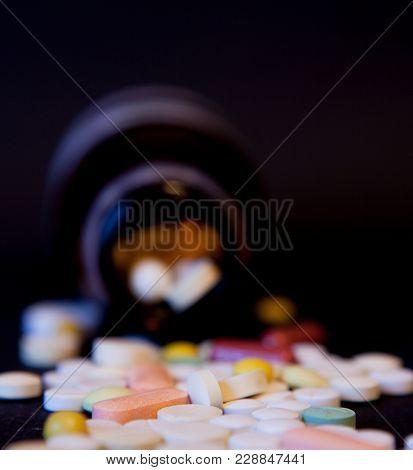 A Bottle Of Spilled Pills On Black Background. Levitating Tablets. Tablets On A Dark Background That