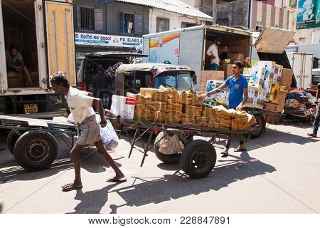 COLOMBO SRI LANKA - DEC 24, 2016: The porter at Pettah Market going against the crowd with full trolley on Dec 24, 2016 in Colombo. Sri Lanka.