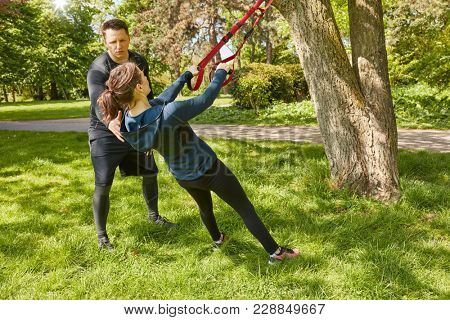 Woman suspension training at park with Personal Trainer