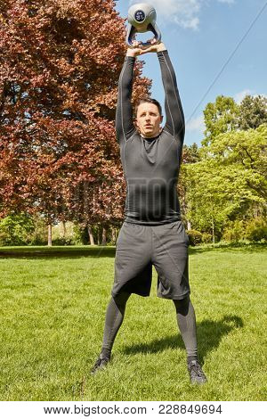 Man weight lift training with kettlebell at the park