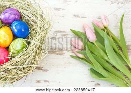 Pink Tulips With Easter Eggs In A Nest On Rustic Wooden Background