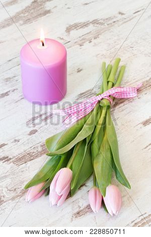 Bunch Of Pink Tulips With Candle On Rustic Wooden Background