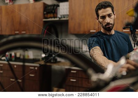 Bicycle Mechanic Assembling A Bike In Workshop