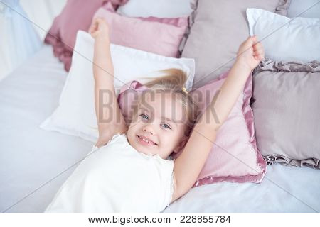 Close-up Little Girl Waking Up With Stretching Arms While Awake Lying On White Bed Linen.