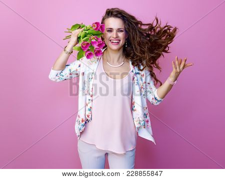 Cheerful Trendy Woman On Pink Background With Bouquet Of Tulips