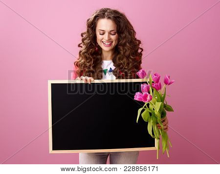 Smiling Woman With Bouquet Of Tulips Looking At Black Board