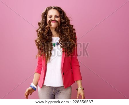 Smiling Trendy Woman Isolated On Pink Making Mustache From Hair