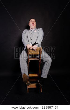 Handsome Man In Gray Suit With Microphone Against Black Background On Studio Sitting On Chair. Toast