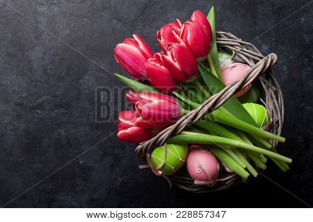 Red tulip flowers bouquet and easter eggs. Easter greeting card. Top view with space for your greetings on blackboard
