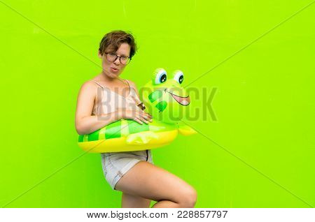 Young Woman With Inflatable Circle Frog On A Background Of Green Wall Fooled Around And Curled Her L