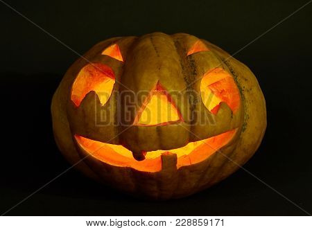 Monster Carved On A Pumpkin Halloween. Inside Lit By Candle