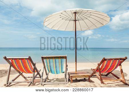 Vacation Holidays Background Beach Lounge Chairs Under Umbrella On Beach.