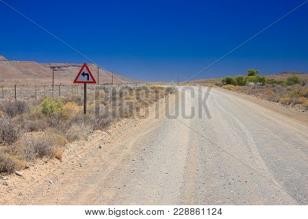 Desert Landscape View Of A Sharp Left Turn Sign On A Dirt Road In The Karoo Of South Africa