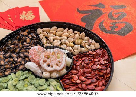 Chinese snack tray with red packet and Chinese calligraphy word means luck