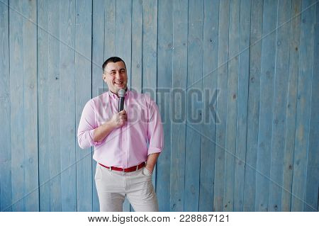 Handsome Man In Pink Shirt With Microphone Against Blue Wooden Wall Background On Studio.  Laughs Fa