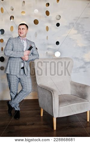 Handsome Man In Gray Suit With Microphone Against Chair Background On Studio. Toastmaster And Showma