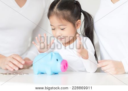 Parents Are Teaching Daughter On Saving Money And Financial Planning.