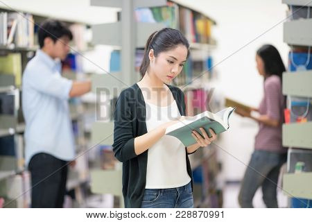 Lovely Woman Stand Reading Book In The Library. Group Of New Generation People Doing Research Projec