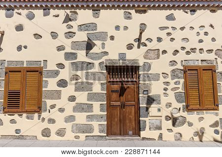 The Facade Of A Country House With Closed Wooden Door And Windows