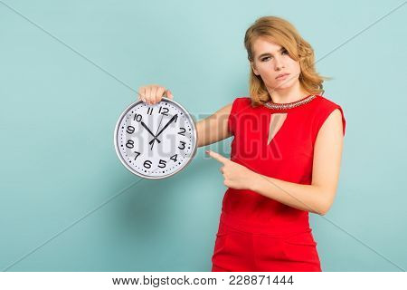 Portrait Of Blonde Woman In Red Isolated On Blue Background Holding Clocks And Pointing At Them Time