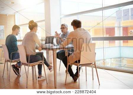 Teacher meeting around table with students
