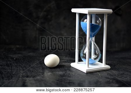 Still-life Nature Morte With White Egg And Sandglass On Black Background